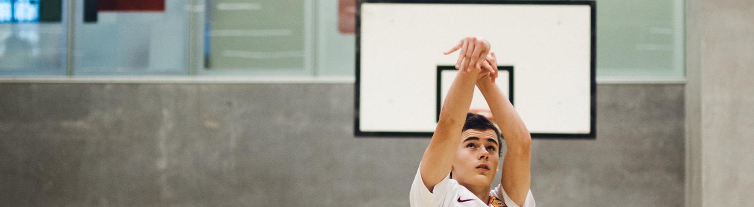 Dreng dunker bold i basketnet i idrætshallen.