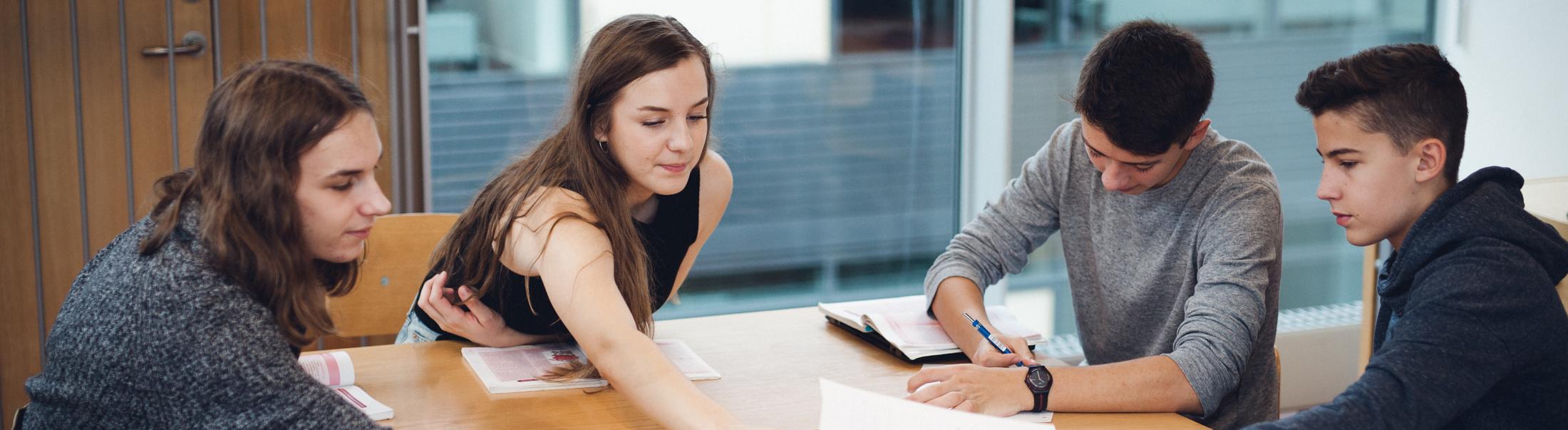 To piger og to drenge sidder sammen i gruppearbejde.