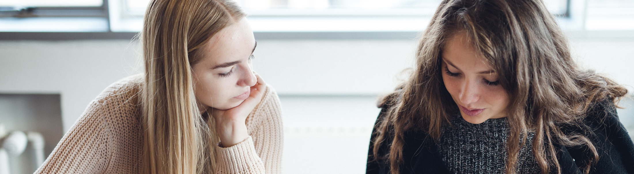 To piger sidder og arbejder ved et bord.