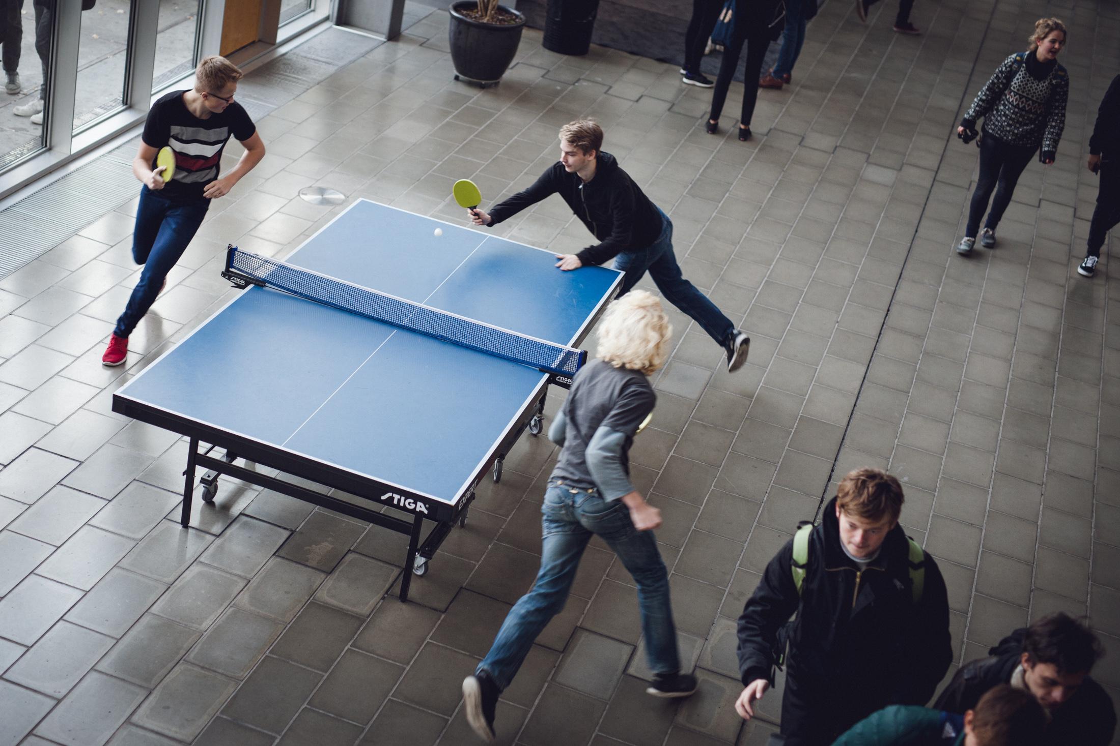 Foto af elever der løber rundt om bordtennisbord i forhallen og spiller bordtennis.