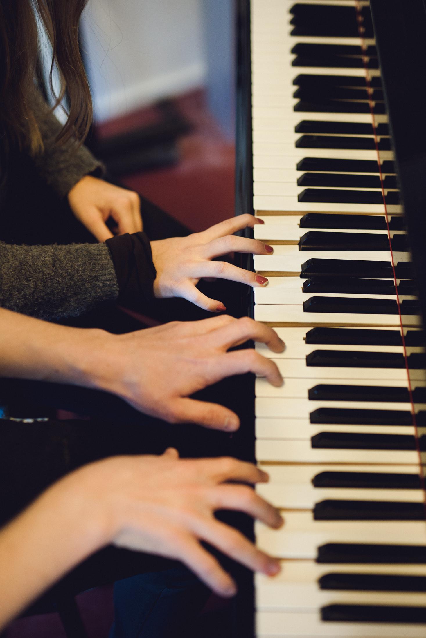 Foto af fire hænder på klavertastatur.