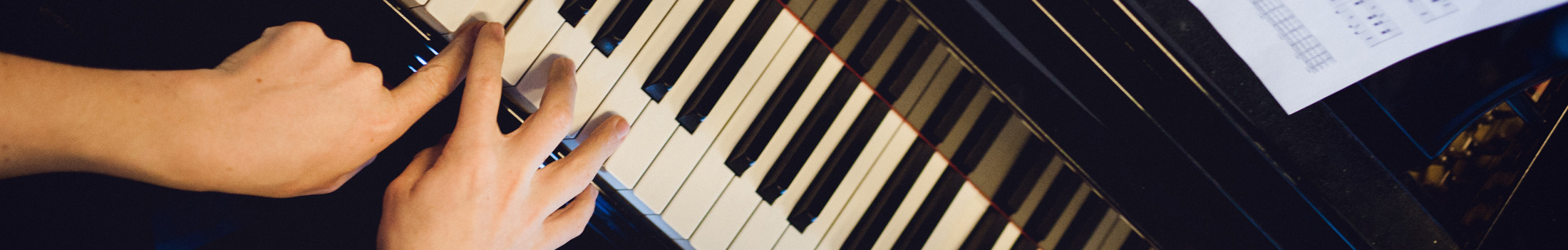 To hænder spiller på klavertastatur