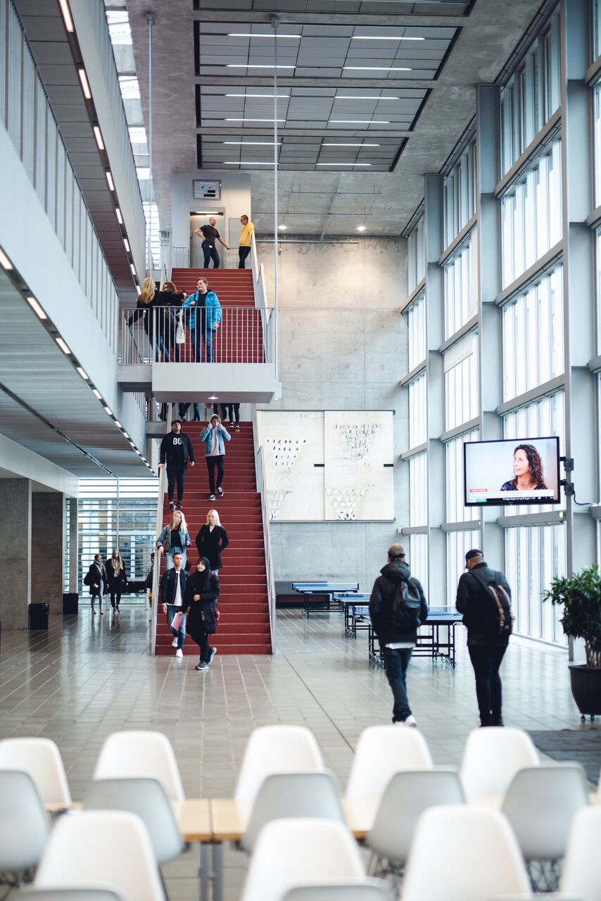 Foto af skolens forhal med den røde trappe i baggrunden.