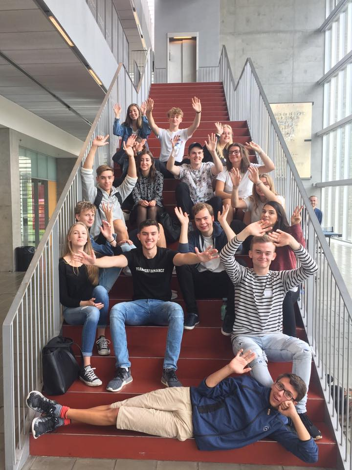 Foto af 16 tutorer der sidder på hovedtrappen i forhallen og byder velkommen.