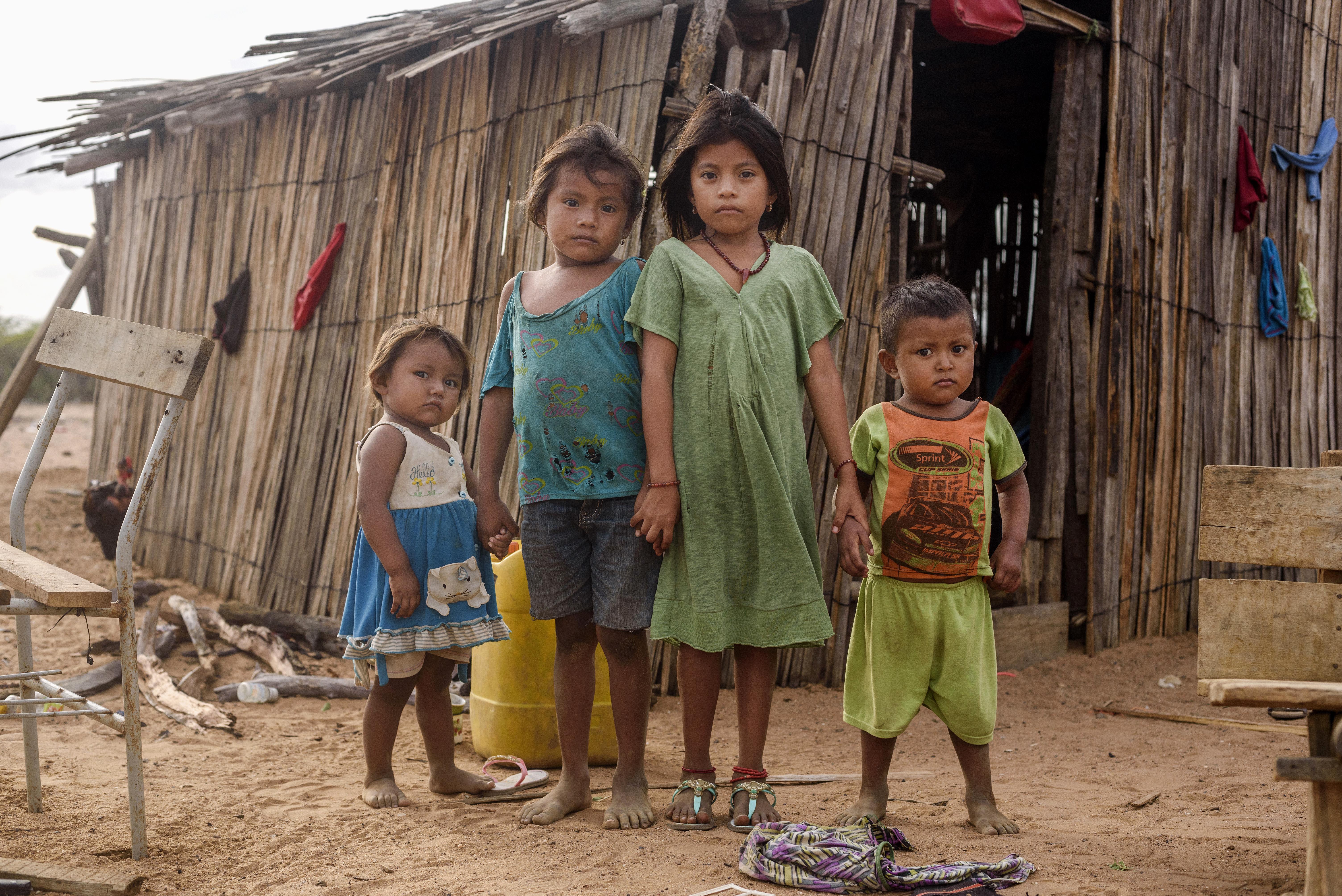 foto af fire børn foran faldefattig hytte