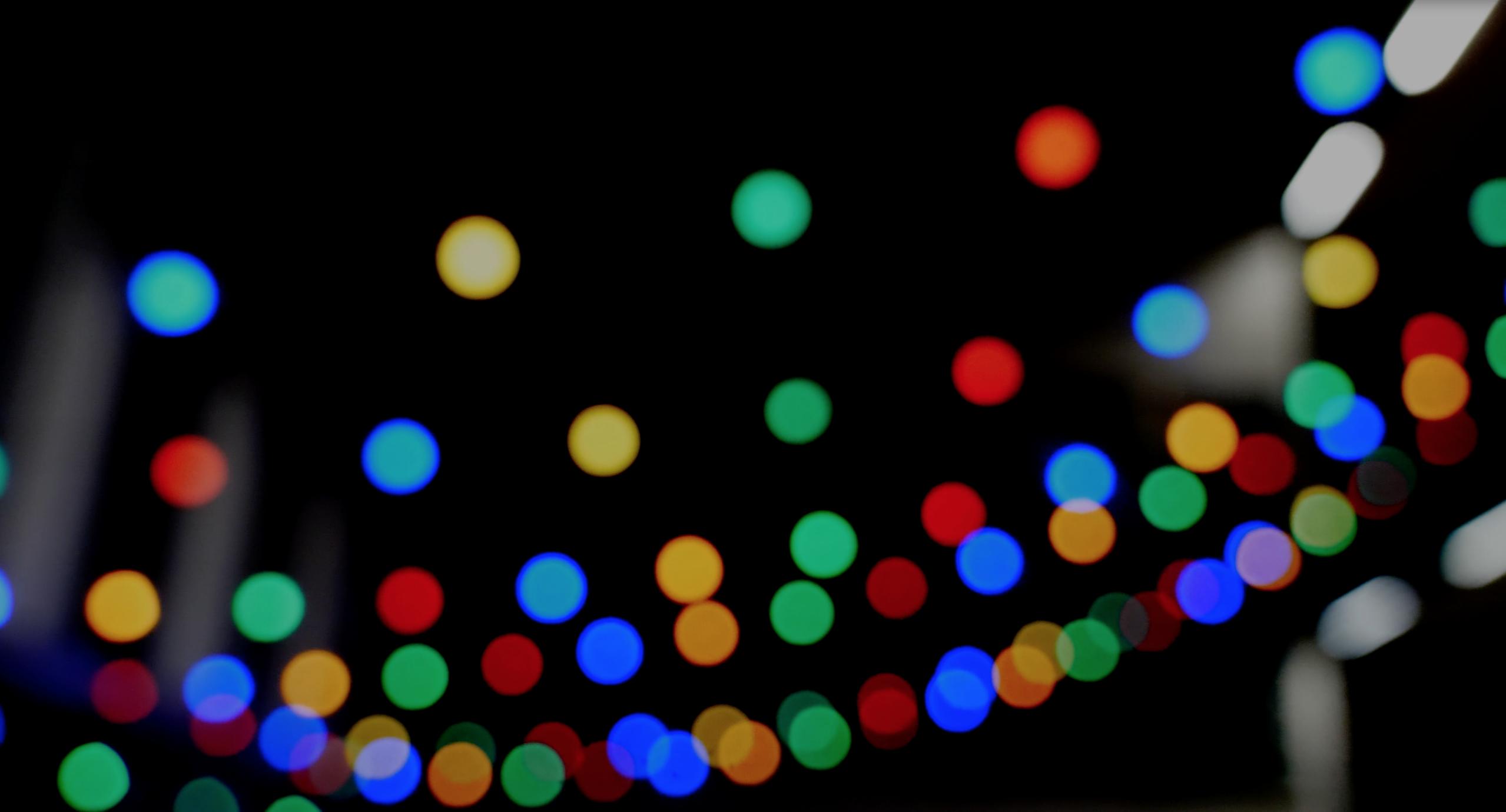 Foto af runde farvede prikker på sort baggrund.