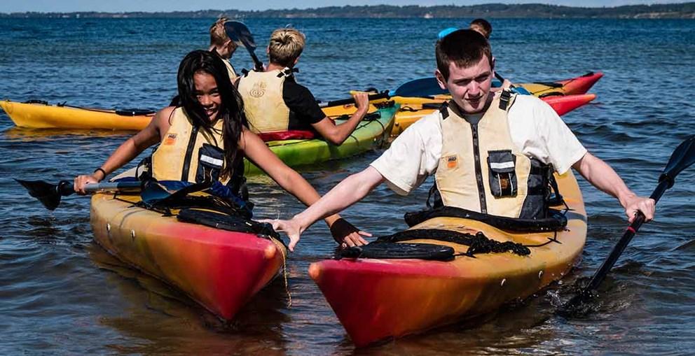 Foto af elever der sidder i kajakker ude på vandet.