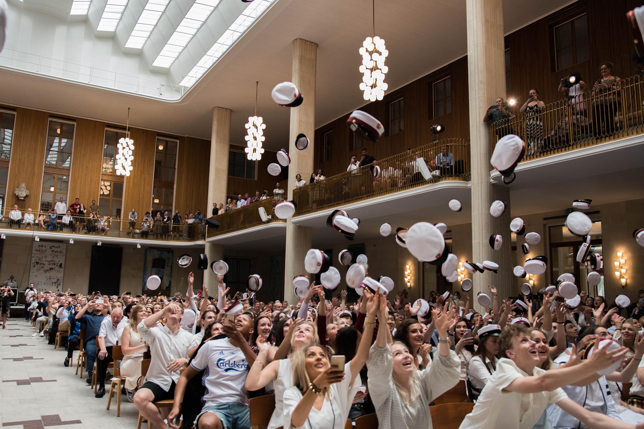 Foto af studenterne i Frederiksberg Rådhus festsal til translokation. De kaster studenterhuerne op i luften.