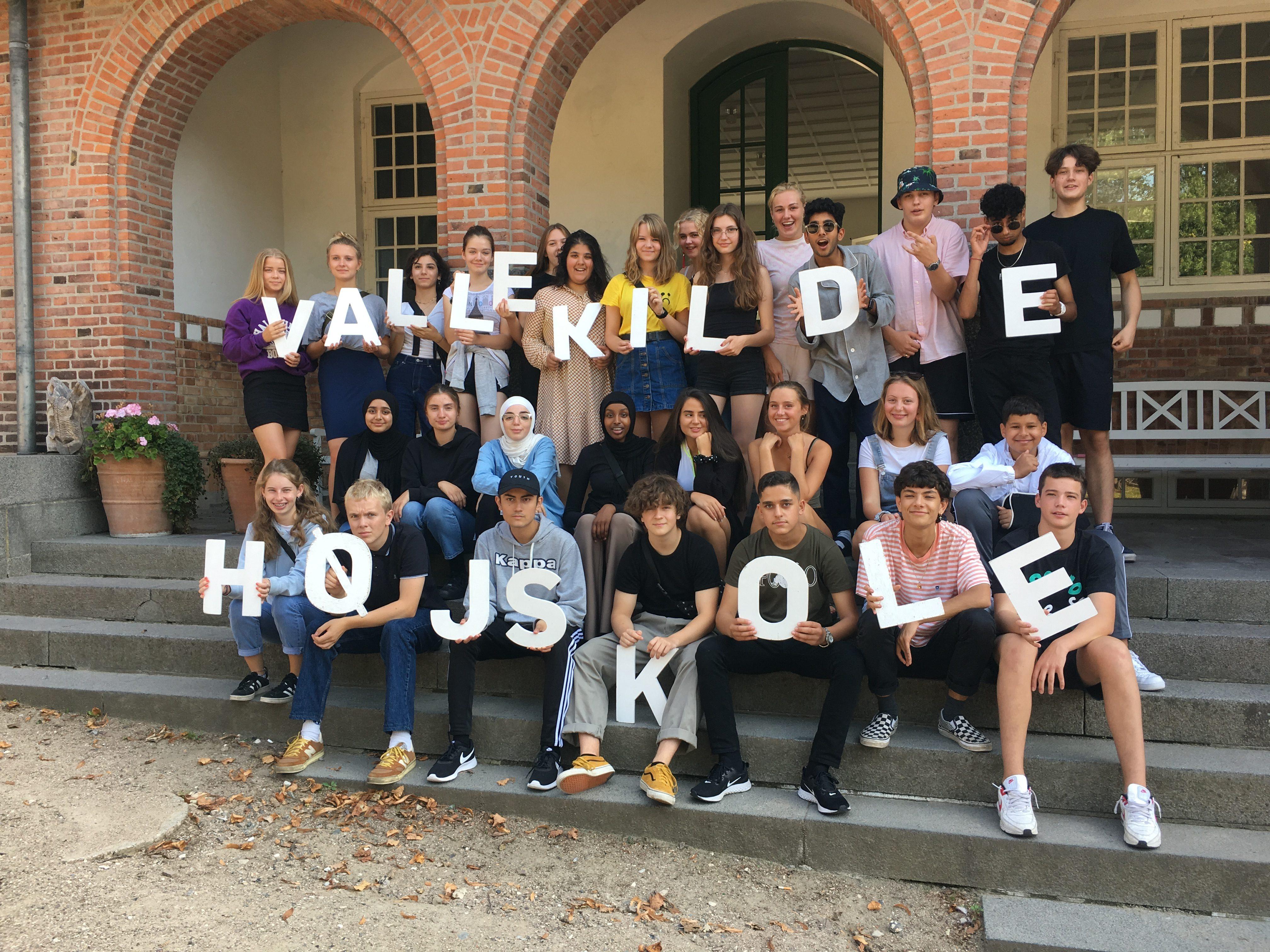 Foto af elever der sidder på trappen ved indgangen til Vallekilde Højskole